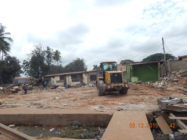 A tractor demolishing illegal structures in road way